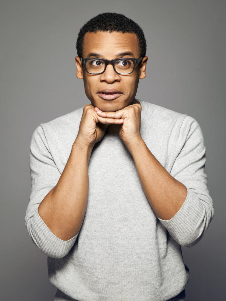 Jordan Carlos wearing glasses and resting chin on folded hands